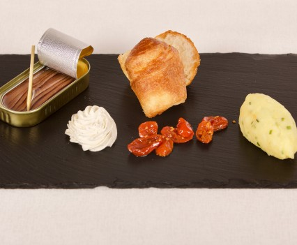 Gold selection of Cantabric anchovies served with toasted bread and herbs flavored butter