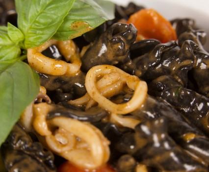 Squid ink lilies of pasta with calamari, tomatoes and marjoram